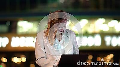 Encantadora muchacha freelancer sentada en el patio al aire libre por la noche, trabajando en una laptop, Tiempo ventoso almacen de metraje de vídeo