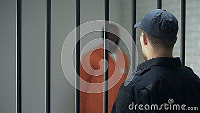 Encargado que mira al criminal peligroso que camina en la célula, cadena perpetua, prisión almacen de video