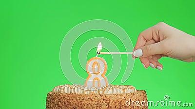Encendiendo una vela número ocho cumpleaños en una deliciosa tarta, pantalla verde 8 almacen de video