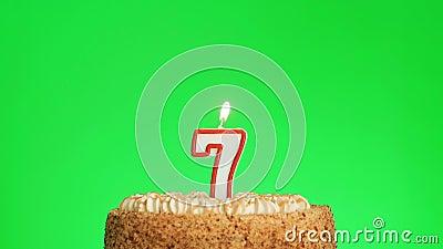 Encendiendo una vela número siete cumpleaños en un delicioso pastel, pantalla verde 7 almacen de video