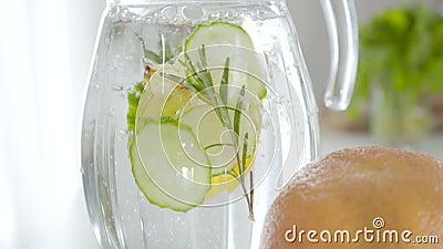 Encerramento do cocktail de detox de plantas herbáceas infuso em jarro transparente Lentidão da água que entra num recipiente de  vídeos de arquivo