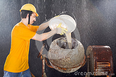 Worker is cleaning cement mixer while big rain is falling