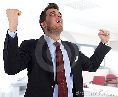 Energetic businessman with arms raised