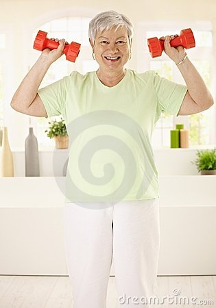 Energetic elderly woman training at home