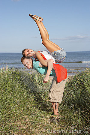 Energetic Young Couple Having Fun In Dunes