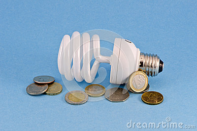 Energy saving light bulb and  coins on azure background