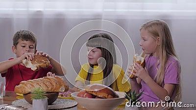 Enfance joyeuse, les petits souriants s'assoient à table et partagent un petit pain en mangeant des bonbons à la fête des enfants banque de vidéos
