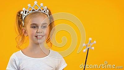 Enfant blond mignon ondulant la baguette magique magique et souriant sur la caméra, les rêves et l'enfance clips vidéos