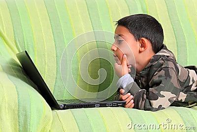 Enfant curieux avec l ordinateur portatif