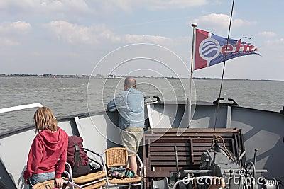 Enfant et homme tenant à l arc d un bateau ce des voiles à l île Griend Image stock éditorial