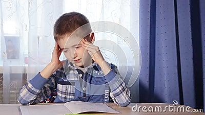 Enfant faisant le mal de tête de devoirs, garçon de fatigue pour faire banque de vidéos