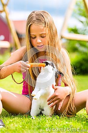 Enfant heureux avec l animal familier de lapin à la maison dans le jardin