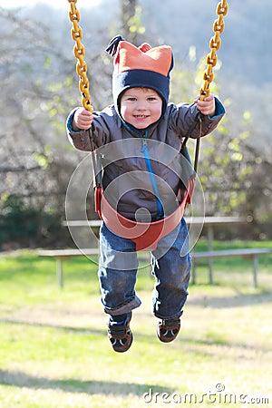 Enfant sur l oscillation à une cour de jeu