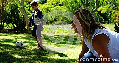 Enfantez écarter la couverture et le fils de pique-nique jouant le football en parc 4k banque de vidéos