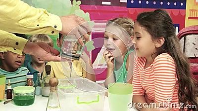 Enfants observant l'animateur effectuer une expérience de la science banque de vidéos