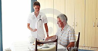 Enfermeira que oferece um bolo a seu paciente video estoque