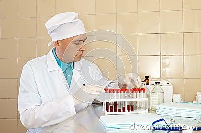 Enfermera de sexo masculino con los tubos de prueba
