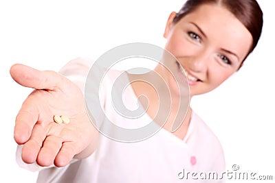 Enfermera hermosa que ofrece dos píldoras
