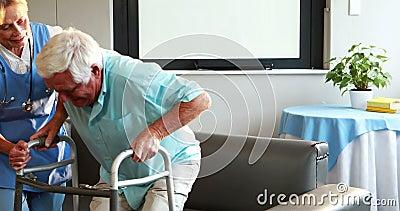 Enfermera que ayuda al hombre jubilado con el caminante metrajes