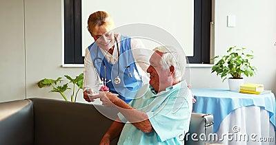 Enfermera que trae la torta para el cumpleaños del hombre mayor almacen de metraje de vídeo