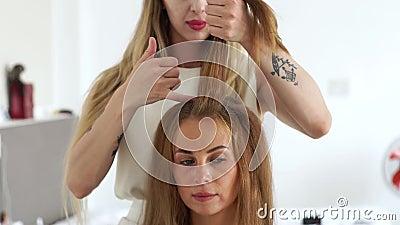 Enfrente a jovem mulher ao criar o penteado no estúdio da beleza Cabeleireiro que faz o penteado da forma à mulher com marrom lon filme