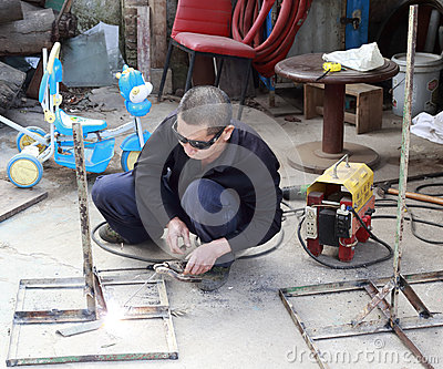 Engaged in metal welding worker Editorial Stock Photo