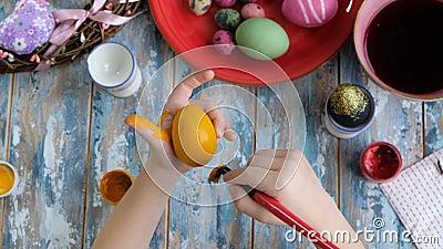 Enge Händchen mit Färbung von Ostereiern mit Ei-Färbung Ansicht von oben stock video footage