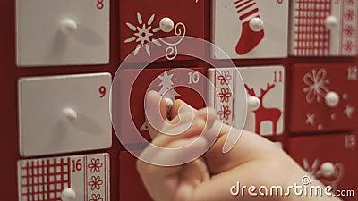 Enge Hände Kleiner Junge nimmt süß vom Advent Calendar House Formular stock footage