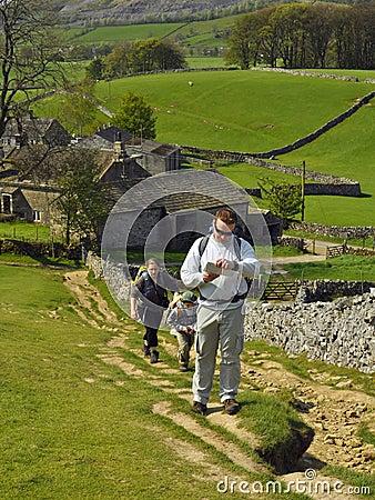 Engels platteland: familie die bergop wandelt