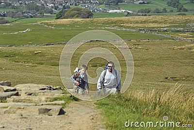 Engels platteland: mens en jongen die bergop wandelen