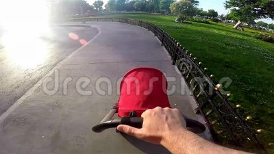Engendre empujar un cochecito de bebé de la barra de la manija en el pavimento urbano almacen de video