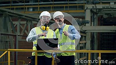 Engenheiros trabalham com um laptop em uma fábrica de tijolos filme