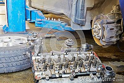 Engine cylinder head and car wheel lie on floor