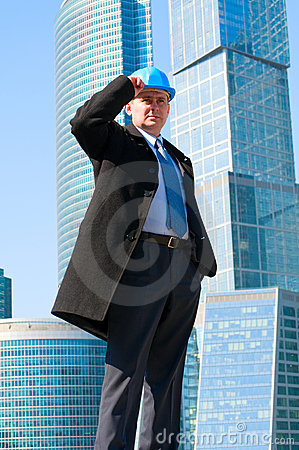 Engineer with blue hard hat standing confidently