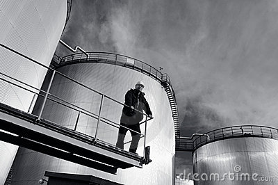 Engineer in hard-hat and oil tanks