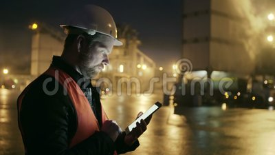 Engineer in hardhat with a tablet computer looks at truck on heavy industry factory. Man in helmet uses tablet PC on heavy industry factory and looks at moving stock video