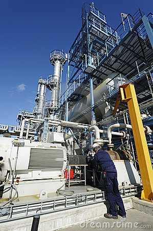 Engineer working on pipelines inside large oil and fuel-refinery.