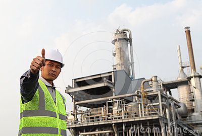 Engineer oil refinery with thumbs up gesture