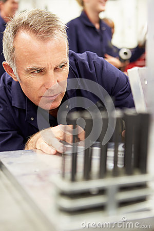 Engineer Studying Component In Workshop Stock Photo