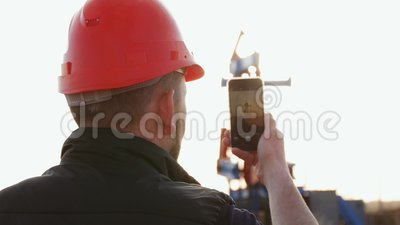 Engineer worker on an oil rig take photo with smartphone. Oil industry using mobile phone communication. Engineer worker on an oil rig take photo with stock video footage