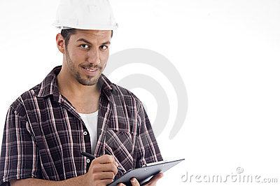 Engineer writing on pad and looking at camera