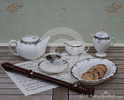 English teacup with saucer, teapot, cream jug, sugar bowl, a cake bowl and a block flute on a sheet of music Stock Photo