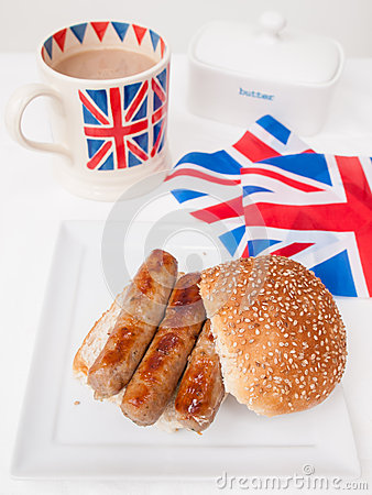 English sausage sandwich with cup of tea and flag