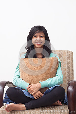 Isolated happy teenager smiling to the camera and holding her pillow at home