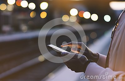 Enjoying travel. Young woman waiting on station platform on background light electric moving train using smart phone in night Stock Photo