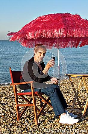 Enjoying wine on beach under parasol