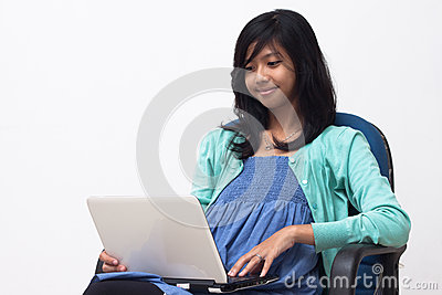 Young business woman holding a laptop and enjoying her work