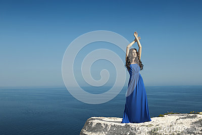 Enjoyment. Fashion Happy beautiful woman with dress over blue sk