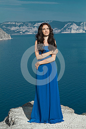 Enjoyment. Fashion Happy beautiful woman in long dress over blue