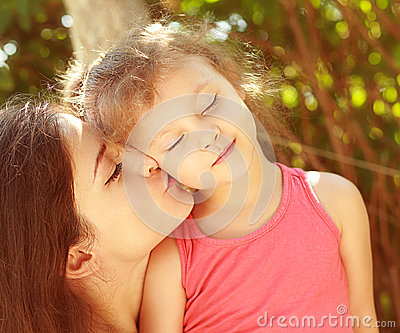 Enjoyment. Mother kissing happy kid